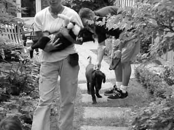 Young woman holding puppy in arms while young man holds on to his puppy in back garden, as an example of positive dog training.